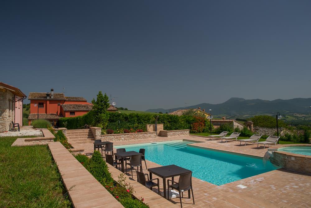Vista panoramica della piscina dell'agriturismo Il Casato con Monte San Vicino sullo sfondo